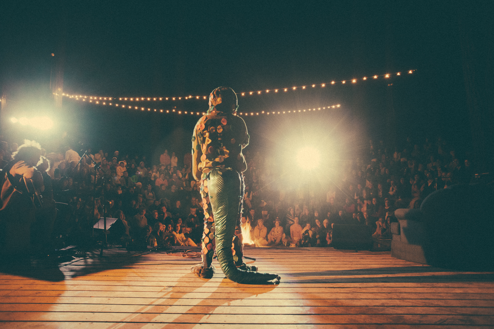 Camper standing alone onstage wearing a dinosaur costume in front of the camp