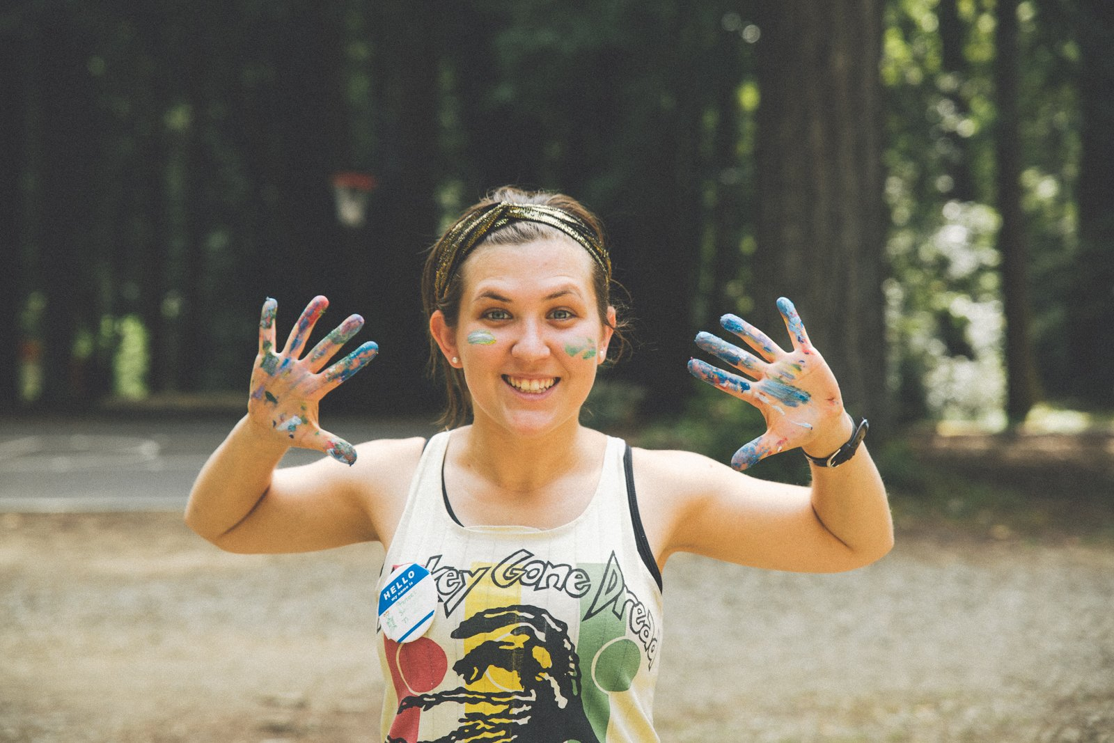 Smiling woman with paint on her hands and face standing in front of a forest