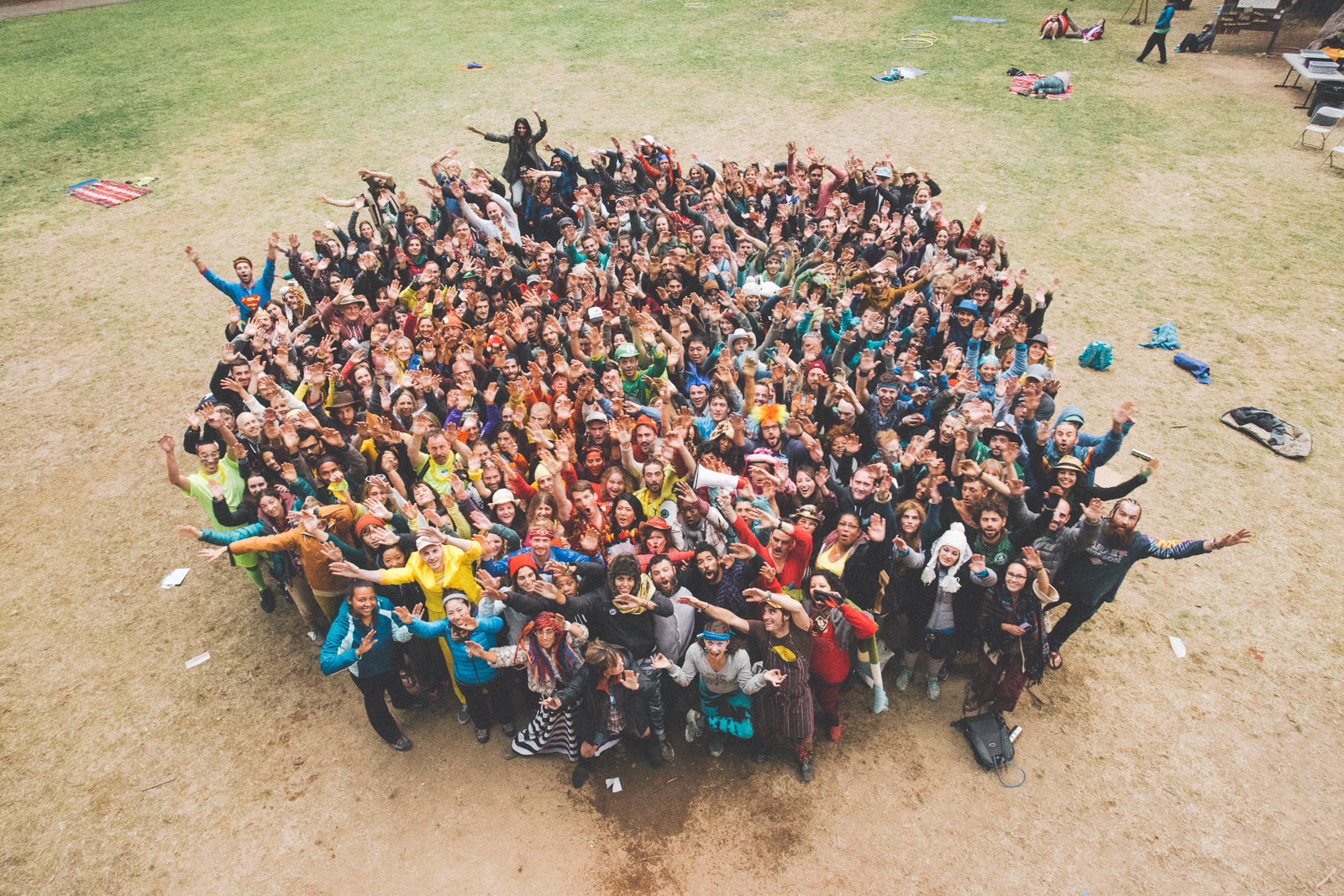 Large group picture of happy campers in a field looking up at the camera