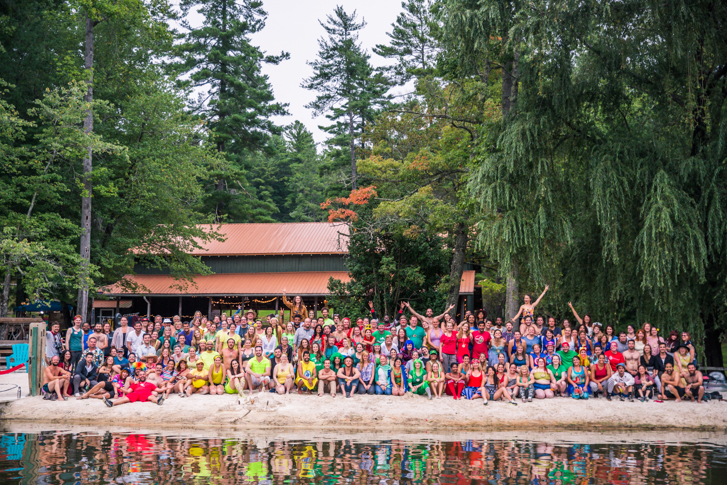 Large group picture of colorfully-dressed campers gathered in front of a lake