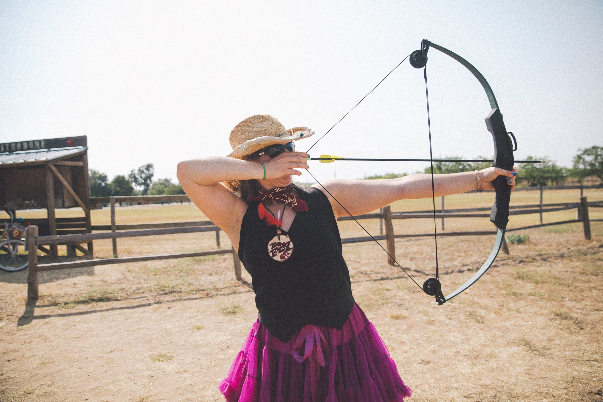 Woman in a cowboy hat shooting a bow and arrow