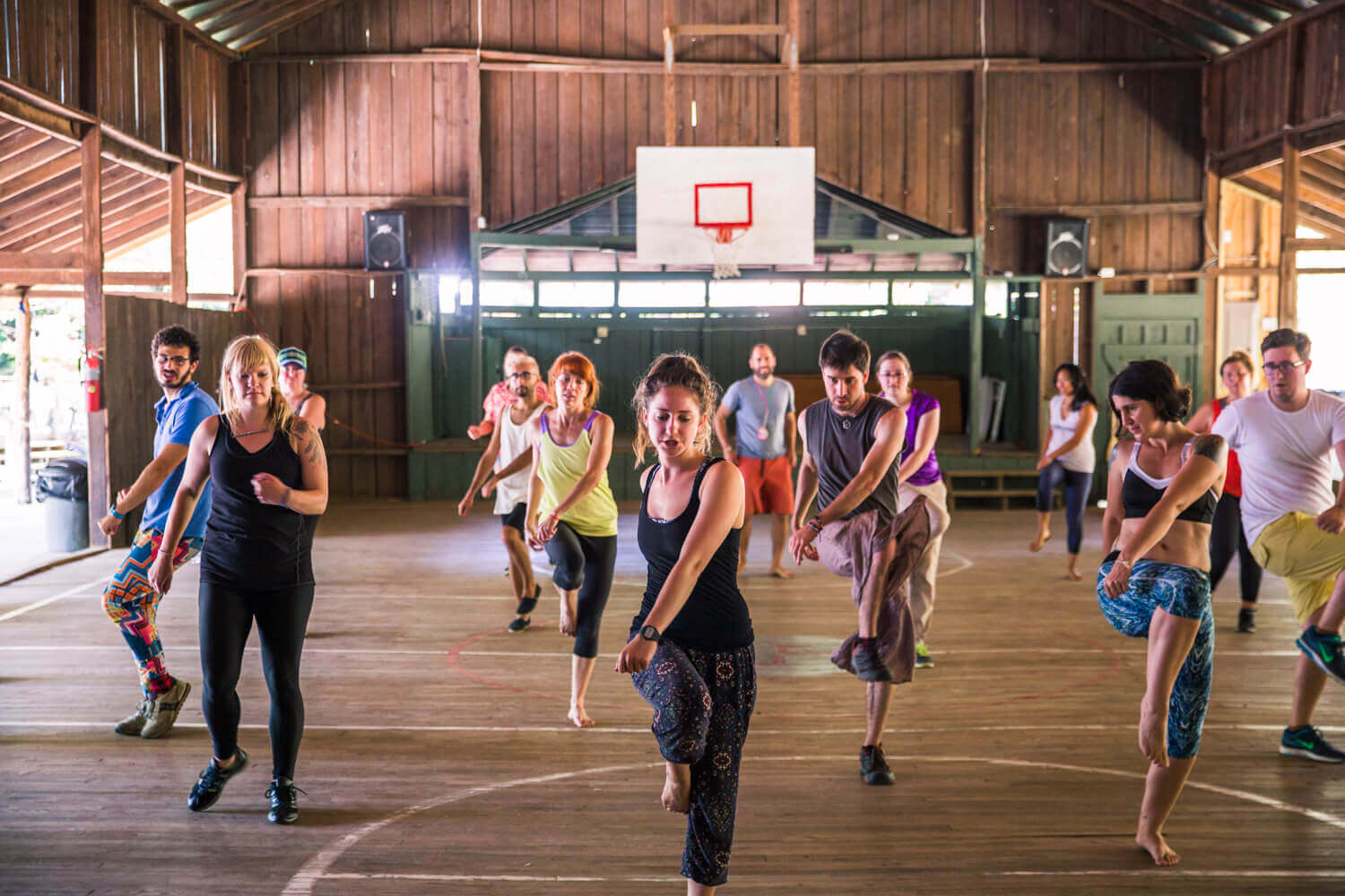 Group of campers dancing on an indoor basketball court