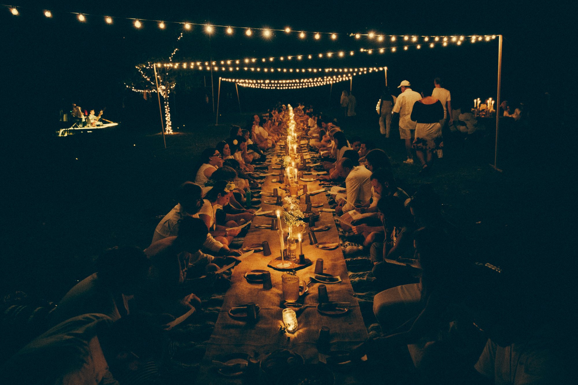 Campers gathered to eat at a long candlelit table for Silent Dinner at Camp Grounded