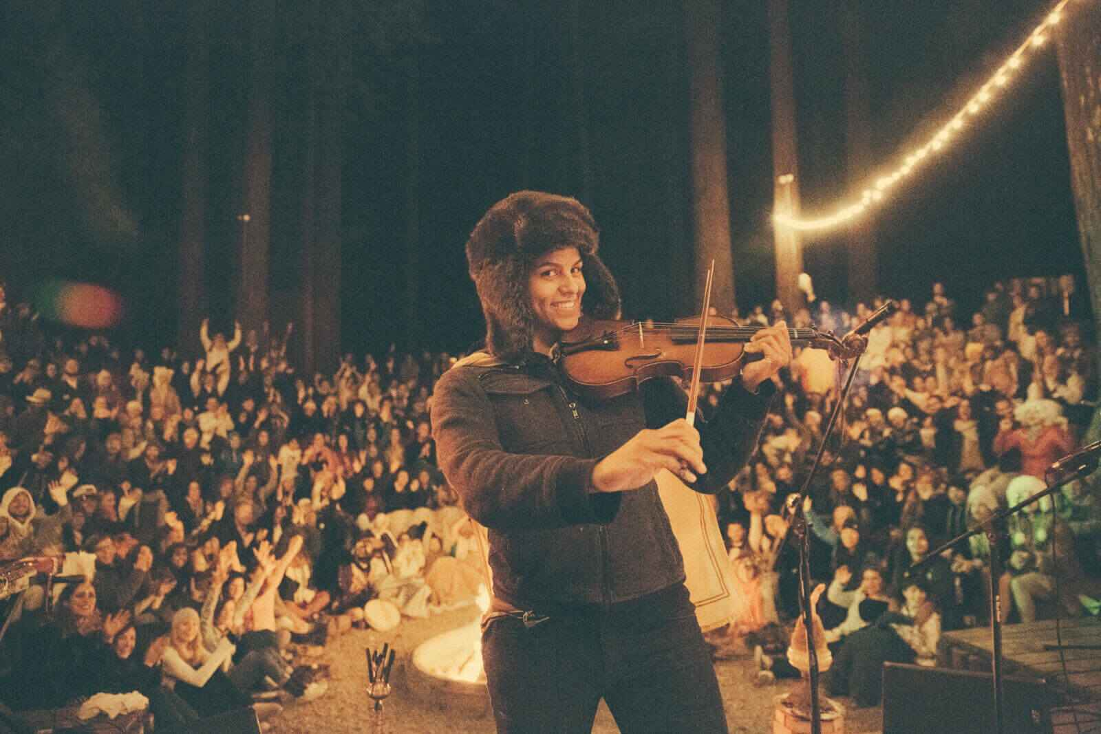 Woman at a campfire playing the violin wearing a fur hat